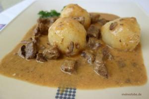 Rahmgulasch mit Cremefraiche zubereitet, mit Knödel serviert.