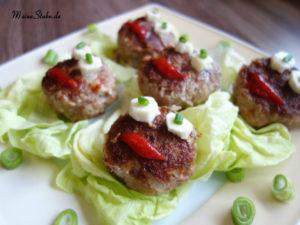 Frikadellen Gesichter auf einem Teller mit Salat serviert