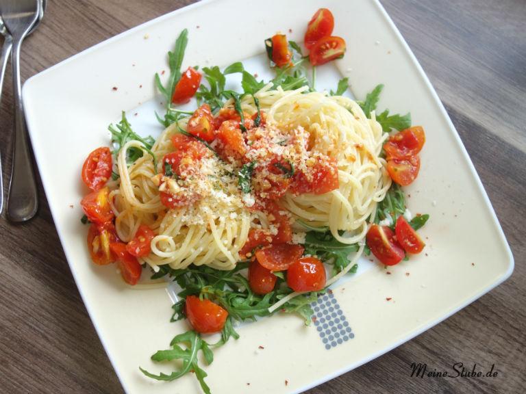 Pasta auf Rucola und Tomaten auf einem Teller serviert