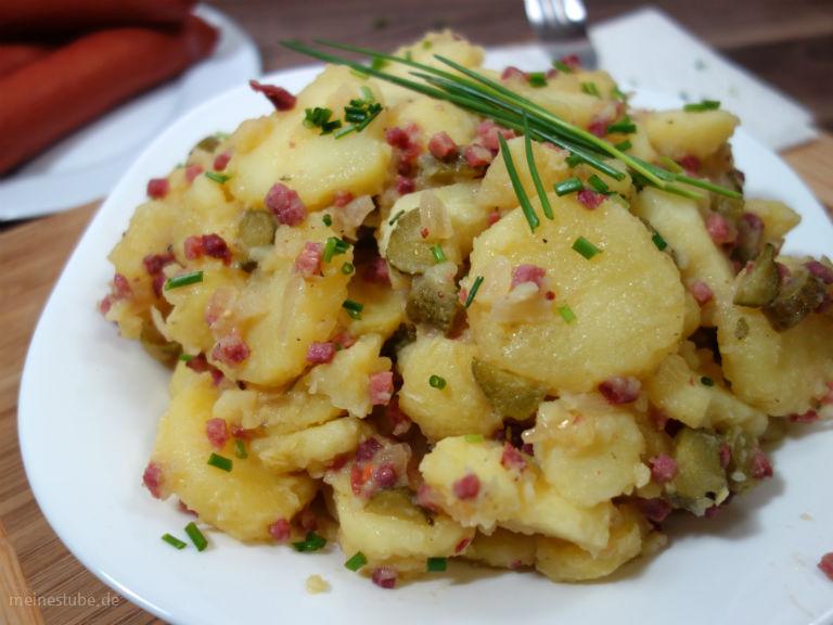Kartoffelsalat mit Speck auf einem Teller serviert.
