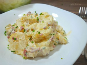 Kartoffelsalat mit Speck, zubereitet mit Mayonnaise auf einem Teller angerichtet.