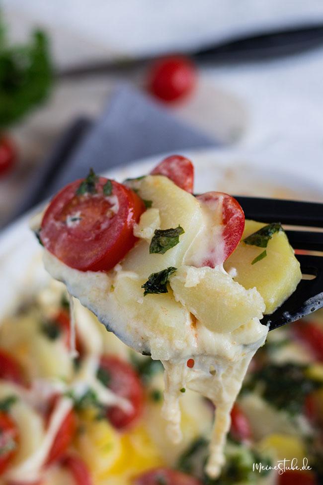 Tomaten-Kartoffel-Mozzarella-gratin auf einer Gabel von meinestube