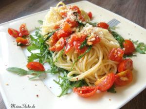 Pasta auf Rucola mit Tomaten und Knoblauch.