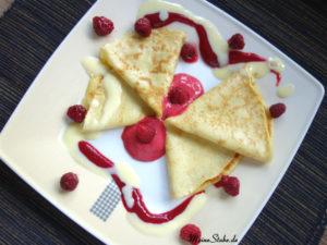 Vanilliecrepes mit Himbeersorbet auf einem Teller serviert.