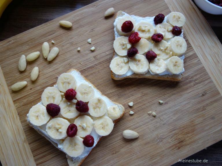 Bananen-Toast mit Joghurt oder Frischkäse belegt mit Himbeeren und mandelstücke