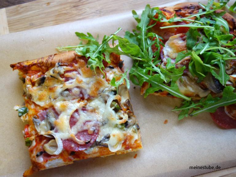 Pizza dick und fluffig mit Rucola serviert