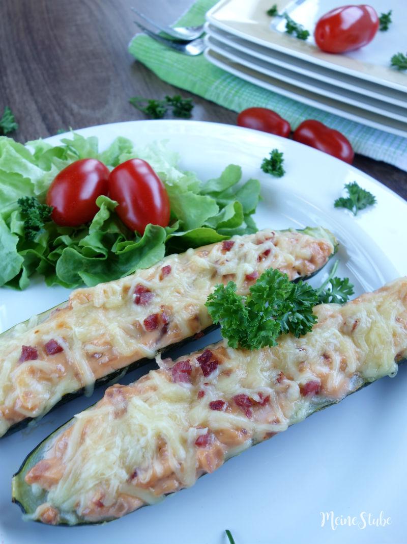 Rezept für Zucchini-Schiffchen mit Frischkäse, Zwiebeln und Speck.