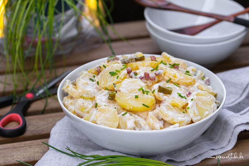 Kartoffelsalat mit Mayonnaise auf einem Gartentisch serviert von meinestube