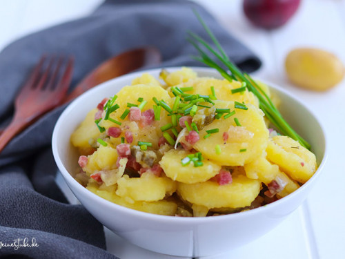 Kartoffelsalat mit Speck und Gurken in weißer Schüssel von meinestube
