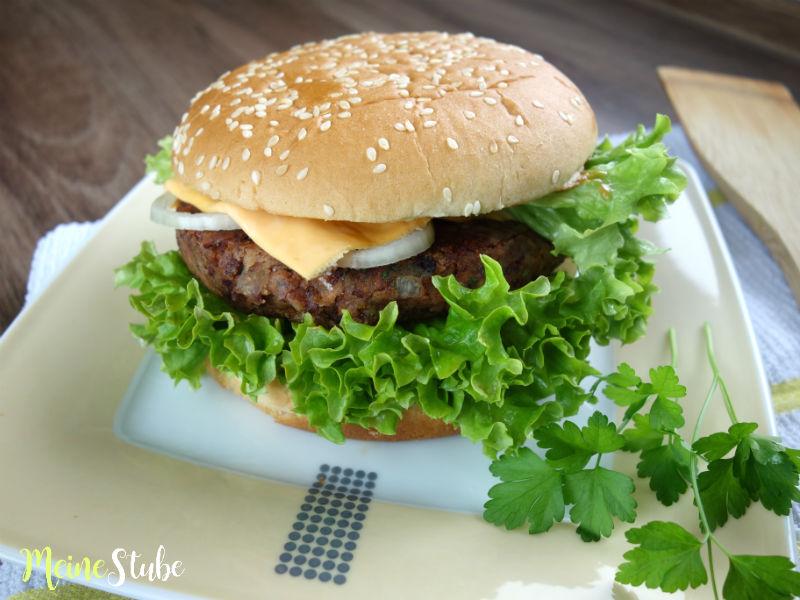 Bohnenburger mit Käse, Zwiebeln und Salat.