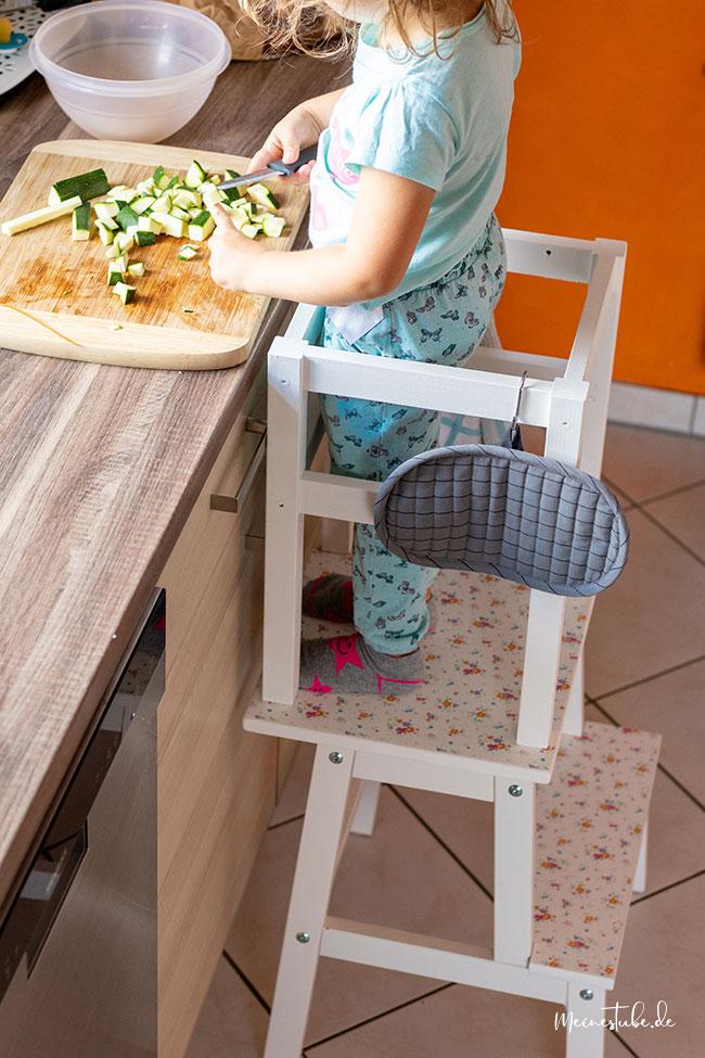 Nia schneidet mit dem Lernturm Gemüse, meinestube