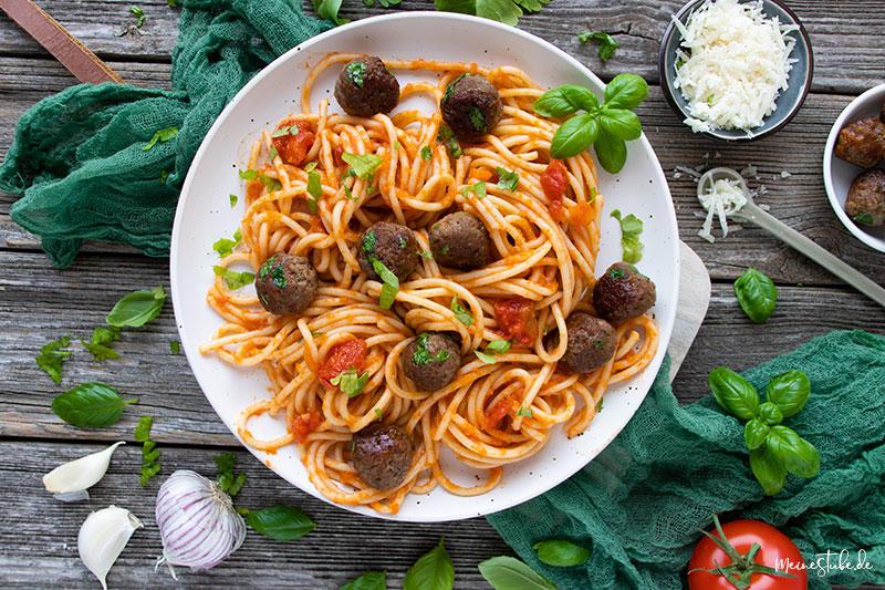 Spaghetti mit parmesan-hackbaellchen auf einem weißen Teller, von Meinestube