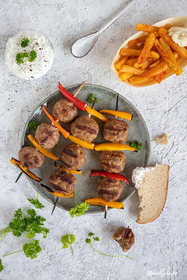 Köfte-Spieße auf einem Teller mit Zaziki und Pommes frites von meinestube